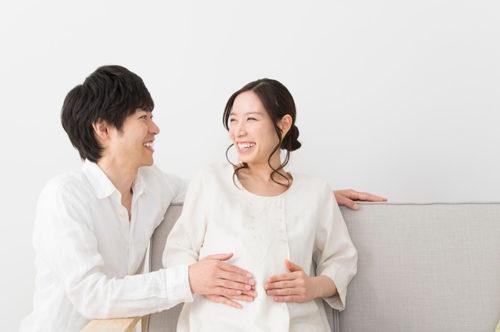 お腹に触れる笑顔の妊婦と夫
