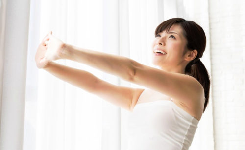 両腕を前に伸ばす女性